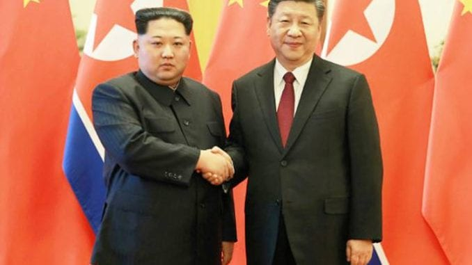 O líder norte-coreano, Kim Jong-Un, cumprimenta o presidente da China, Xi Jinping, em Pequim, durante o primeiro encontro. 28/03/2018 (KCNA/Reuters)